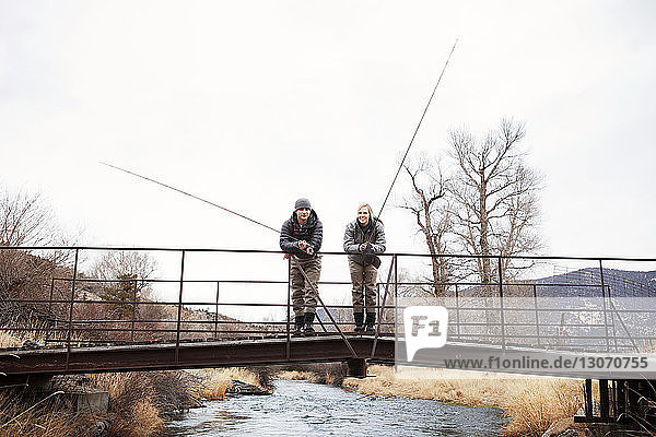 Couple holding fishing rods while standing on footbridge against sky