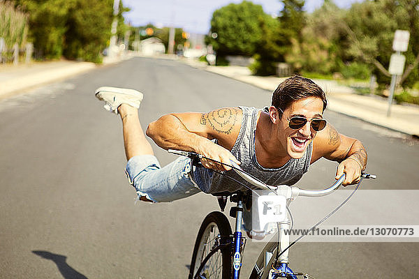 Man performing stunt while riding bicycle on road