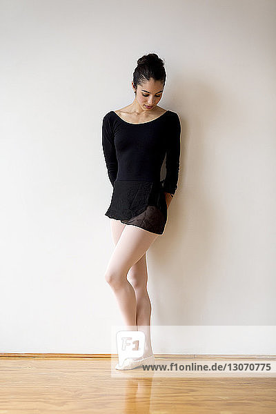 Woman looking down while standing against wall in ballet studio