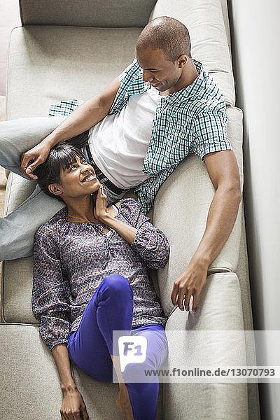 Hochwinkelansicht eines Paares  das sich zu Hause auf dem Sofa entspannt
