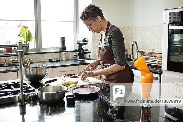 Woman cutting bananas for preparing tart