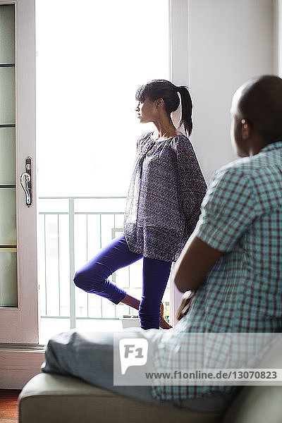 Mann sieht Freundin an  die am Fenster steht