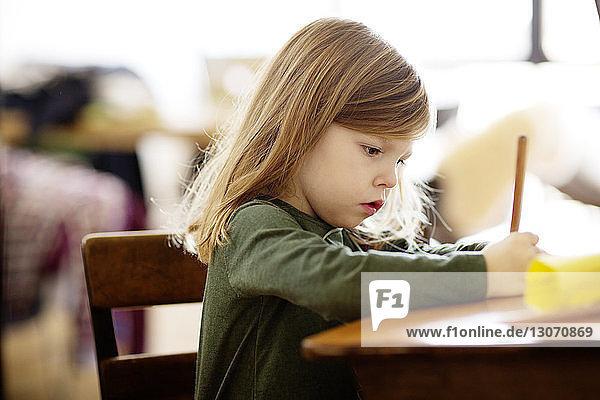 Mädchen schreibt  während sie zu Hause am Tisch sitzt