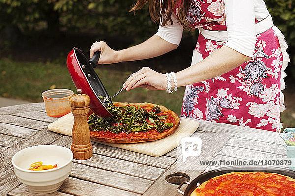 Mittelteil einer Frau  die Beläge auf Pizza legt