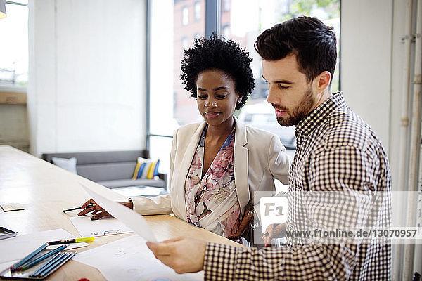 Kollegen diskutieren Dokument während ihrer Arbeit im Büro