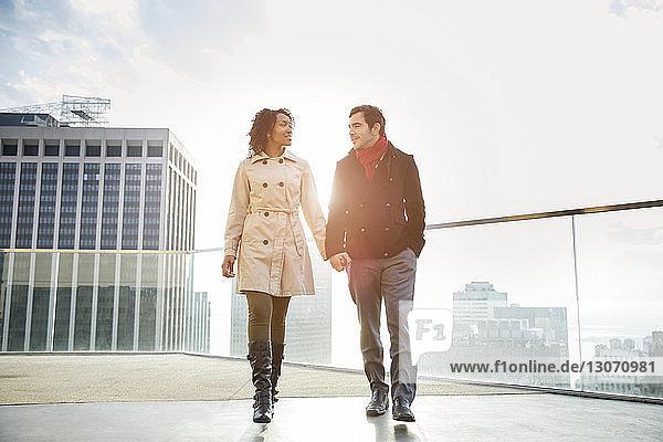 Zärtliches Paar hält beim Spaziergang auf der Terrasse Händchen