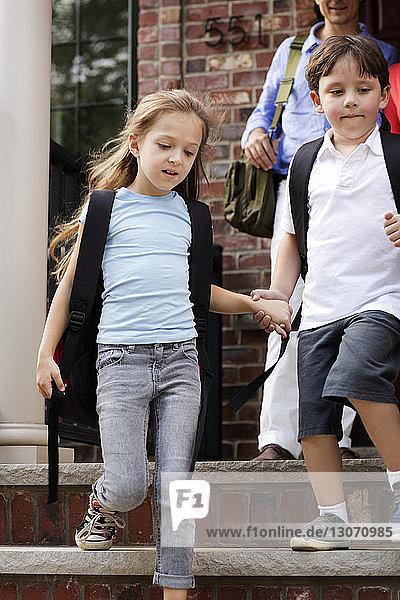 Geschwister halten sich an den Händen  während sie Schritte gegen das Haus hinuntergehen