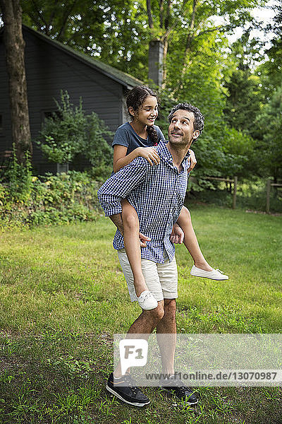 Father piggybacking daughter standing on grassy field at yard