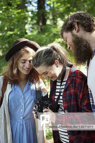 Freunde schauen in die Kamera  während sie im Wald stehen