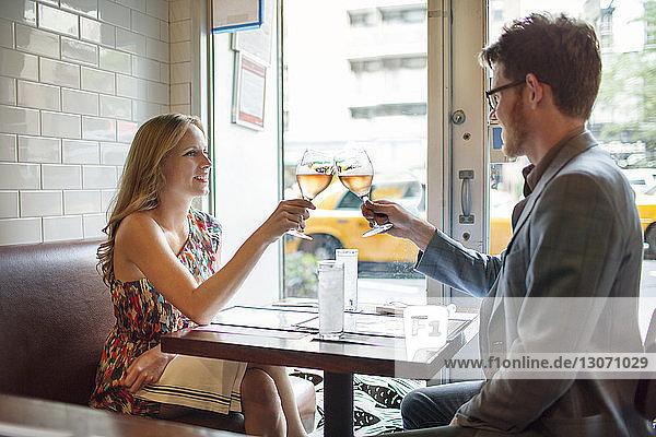 Ein paar Weingläser anstoßen  während man im Restaurant sitzt