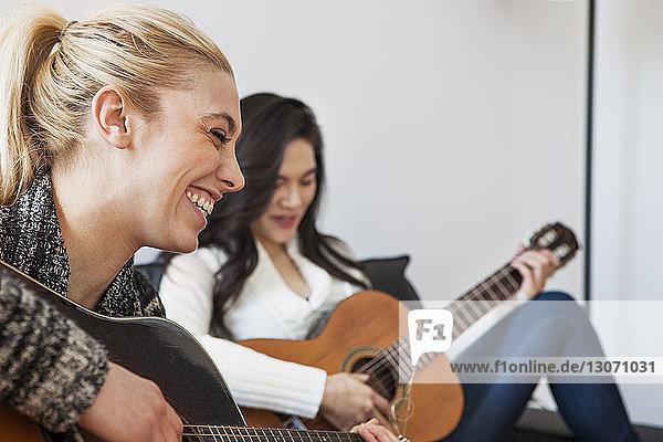 Freunde üben zu Hause Gitarre