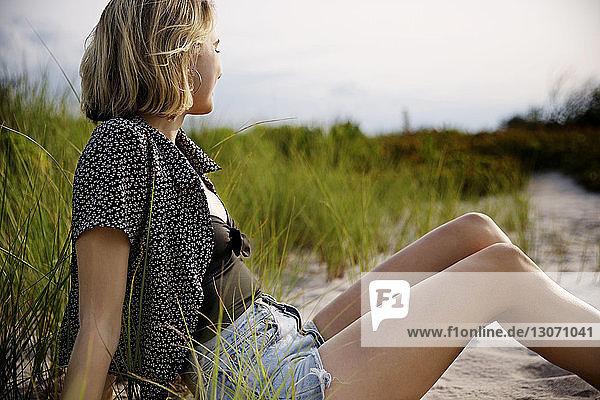Seitenansicht einer auf Sand sitzenden Frau