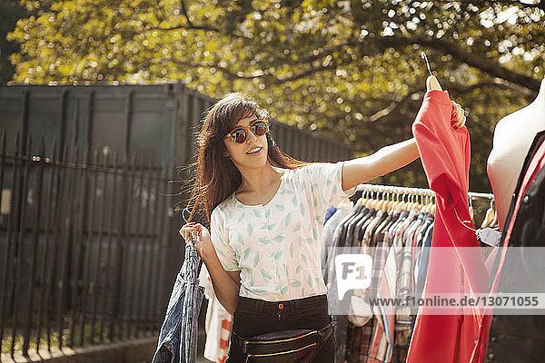 Frau hält Kleid  während sie am Kleiderständer steht