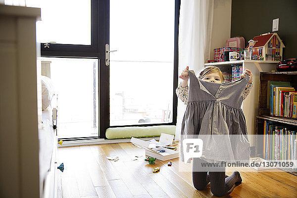Mädchen hält Kleid  während sie zu Hause kniet