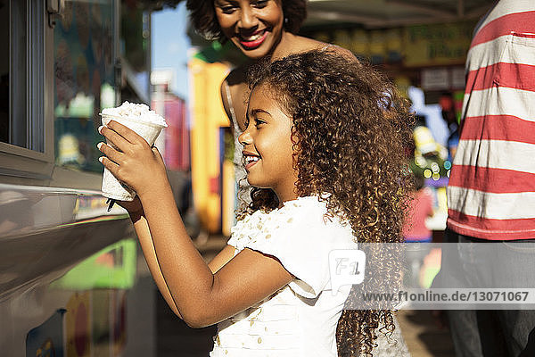 Girl looking at food while standing by food truck in amusement park