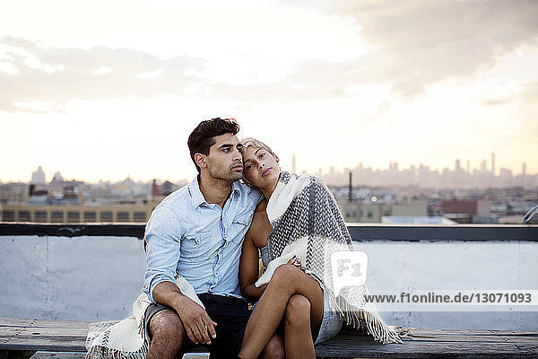 Nachdenkliches  in eine Decke gehülltes Paar ruht auf Gebäudeterrasse gegen den Himmel
