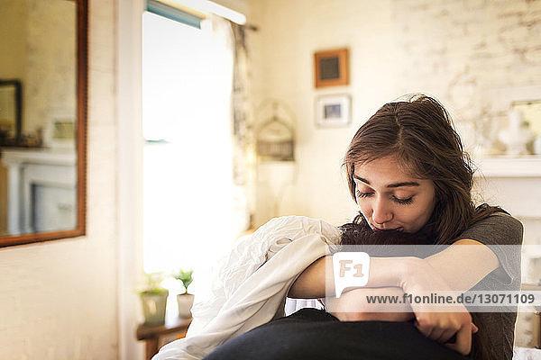 Frau  die den Kopf eines Mannes küsst  während sie zu Hause auf dem Bett sitzt