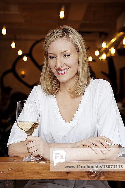 Porträt einer glücklichen Frau mit Weinglas