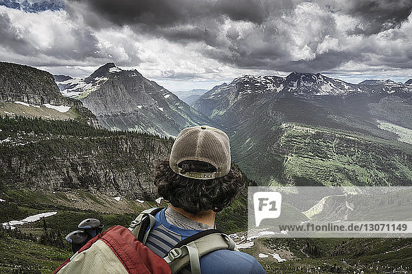 Rear view of hiker standing against mountain range