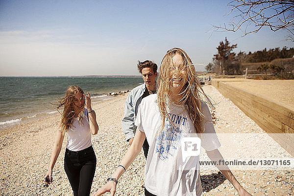 Freunde  die auf Sand am Strand gegen den Himmel laufen