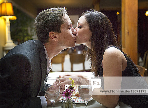 Side view of couple kissing while sitting in restaurant