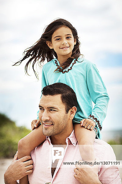Happy father carrying daughter on shoulder against cloudy sky