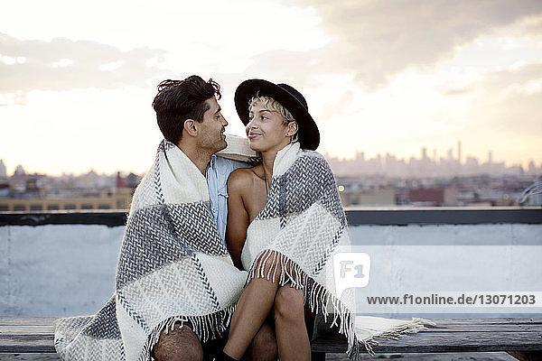 In eine Decke gehülltes Liebespaar ruht sich bei Sonnenuntergang auf der Gebäudeterrasse aus