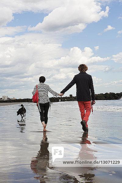 Rückansicht eines Paares  das am Strand am Ufer gegen den Himmel läuft