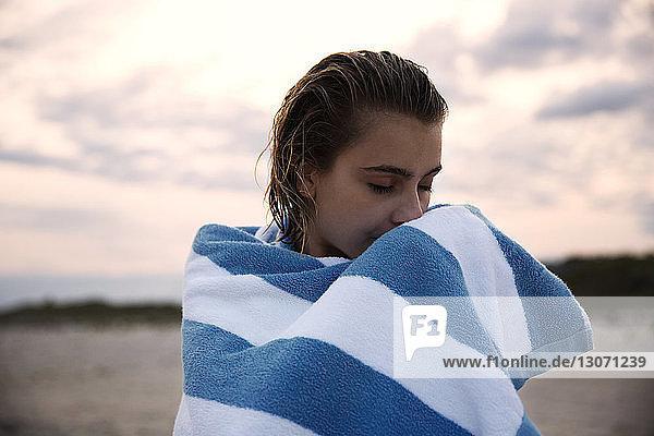 Frau mit geschlossenen Augen  in ein Handtuch gewickelt  gegen den Himmel stehend