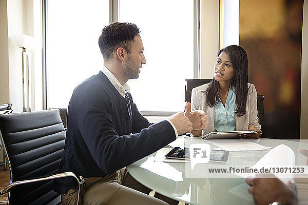 Business people with tablet computer discussing in office