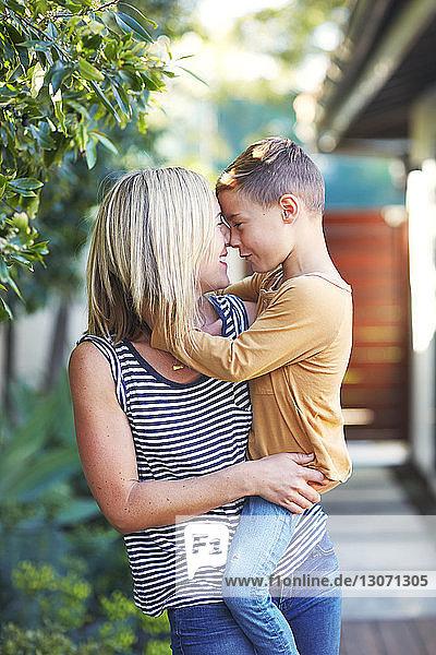 Mutter reibt sich mit ihrem Sohn die Nase  während sie im Hinterhof steht