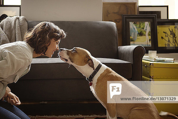 Woman rubbing nose with dog at home