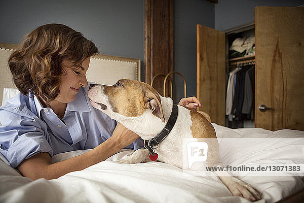 Smiling woman playing with dog on bed at home