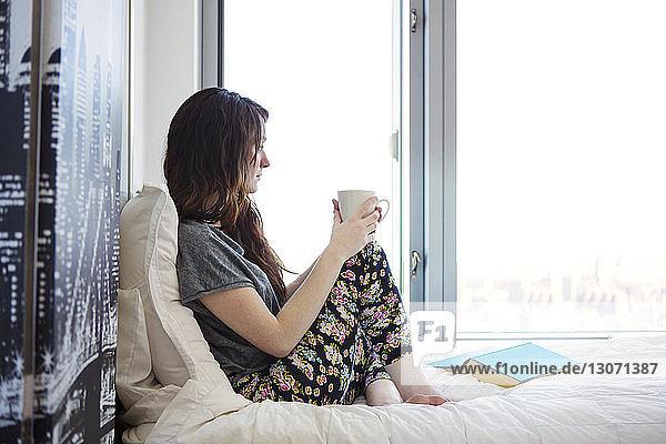 Seitenansicht einer Frau mit Kaffeetasse  die wegschaut  während sie zu Hause auf dem Bett sitzt