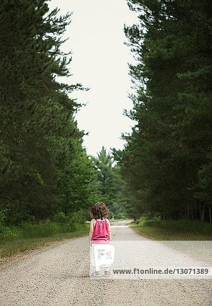 Rückansicht eines auf einem Feldweg stehenden Mädchens