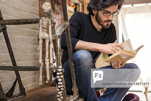 Mann liest Buch  während er zu Hause auf der Treppe sitzt