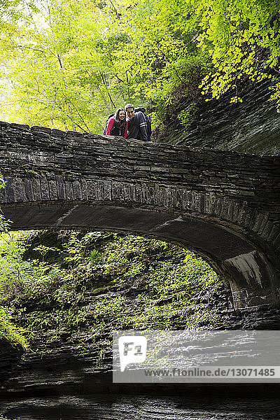 Couple looking down while standing on bridge in forest