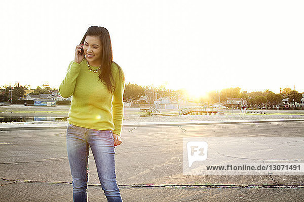 Smiling woman talking on smart phone while standing on road against clear sky