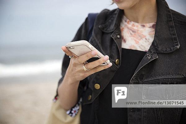 Mitschnitt einer Frau  die ein Smartphone benutzt  während sie am Strand steht
