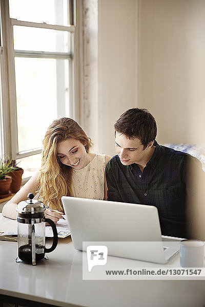 Smiling couple looking down while sitting with laptop computer at home
