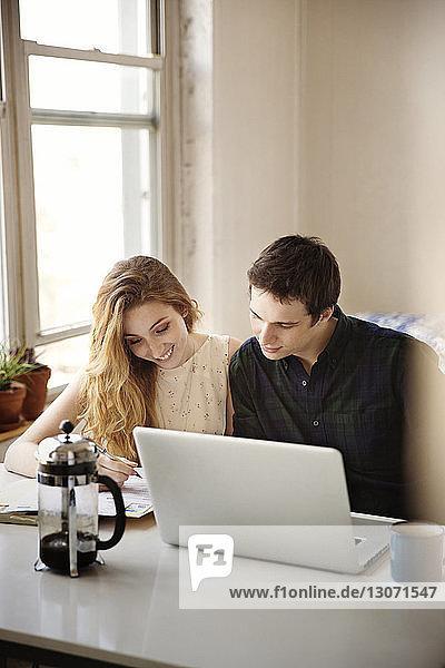 Lächelndes Paar schaut nach unten  während es zu Hause mit einem Laptop-Computer sitzt
