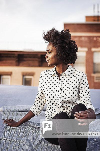 Lächelnde Frau sitzt auf Gebäudeterrasse gegen den Himmel