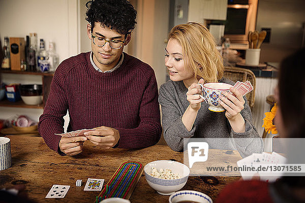 Friends playing cards while having coffee at home