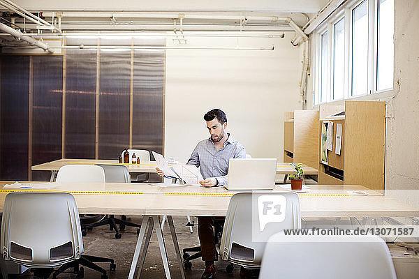 Frau betrachtet Dokument bei der Arbeit im Büro