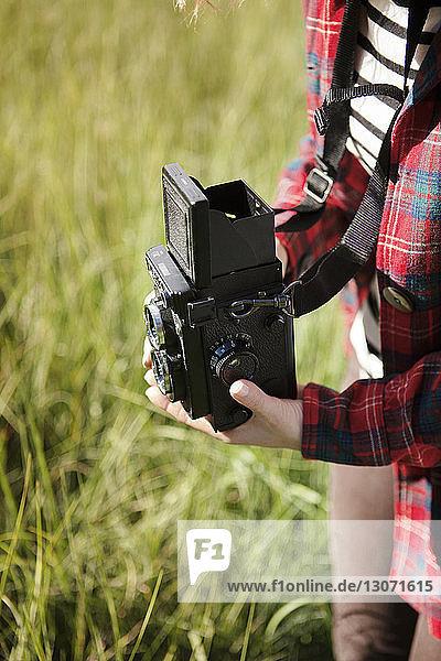 Ausgeschnittenes Bild einer Frau  die die Kamera hält  während sie auf dem Feld steht