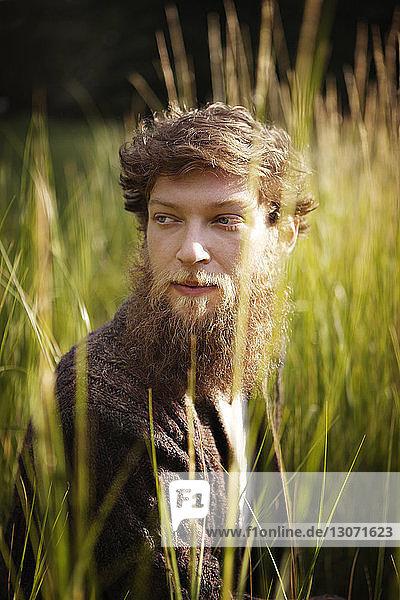 Nachdenklicher Mann schaut weg  während er im Grasfeld sitzt