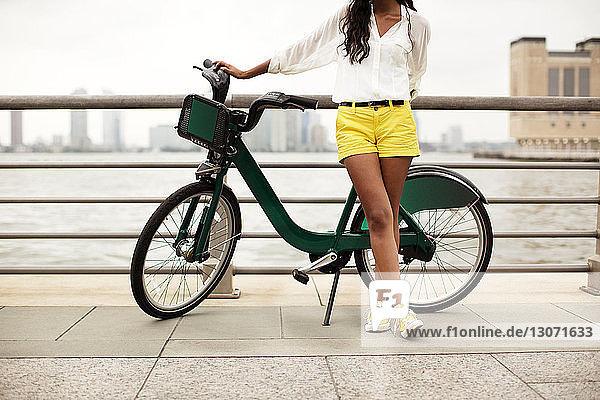 Niedriger Teil einer Frau mit Fahrrad  die gegen ein Geländer steht