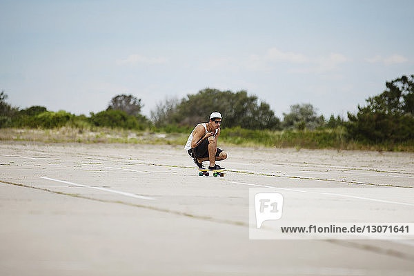 Man performing stunt on skateboard at field against sky