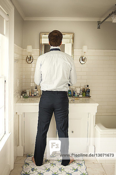Rear view of man getting dressed while standing at mirror in home