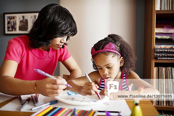 Mother assisting daughter in drawing on table at home